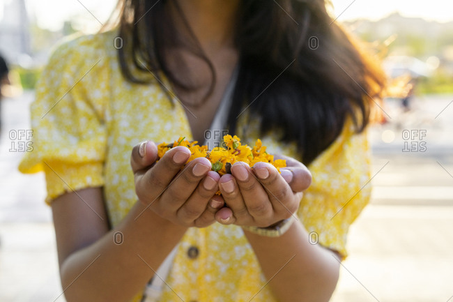 Young woman holding flowers in cupped hands in city during summer