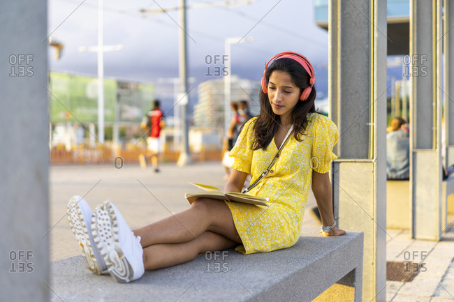 Young woman listening music while reading book on concrete bench in city