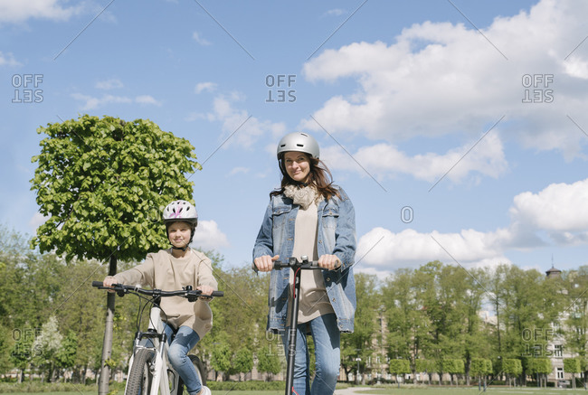 Girl cycling while mother riding motorcycle against sky in city park