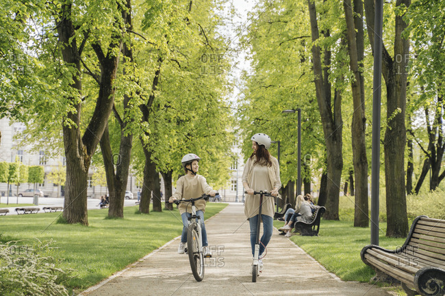 Girl cycling while mother riding electric scooter on road in city park