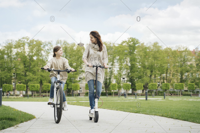 Girl cycling while mother riding electric scooter in city park