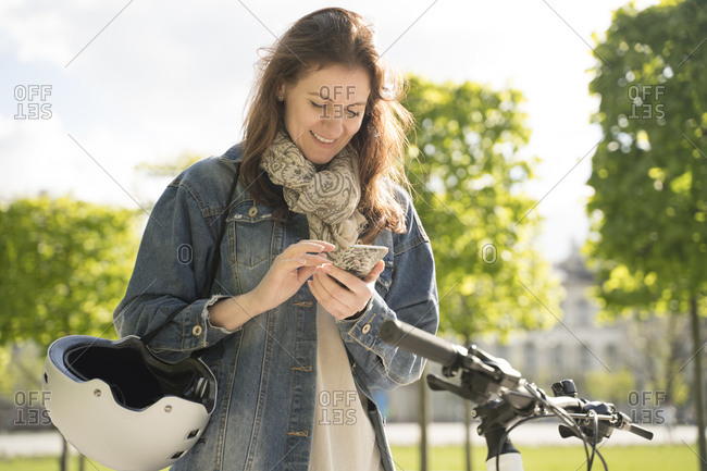 Smiling woman with helmet and bicycle using smart phone while standing in city park