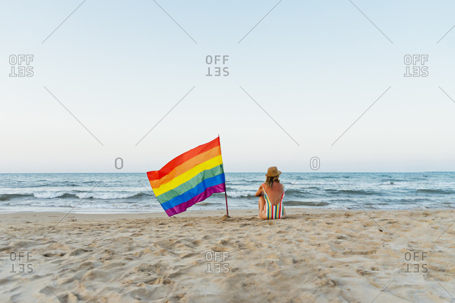 Mature woman sitting on the beach with gay pride flag