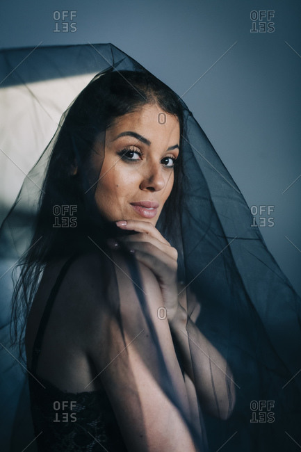 Close-up of young woman wearing black veil standing against wall at home