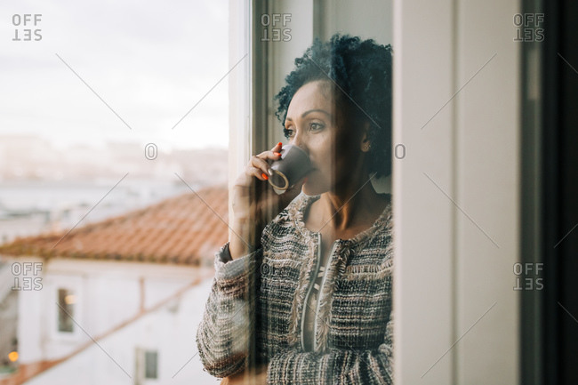 Woman drinking coffee while looking through window at home seen through glass door