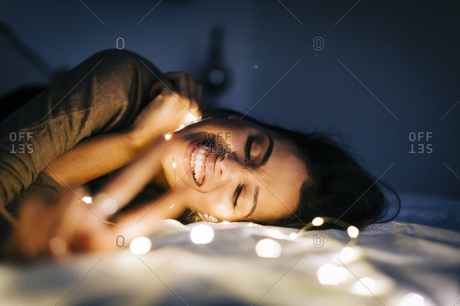 Cheerful young woman with illuminated string lights lying on bed at home