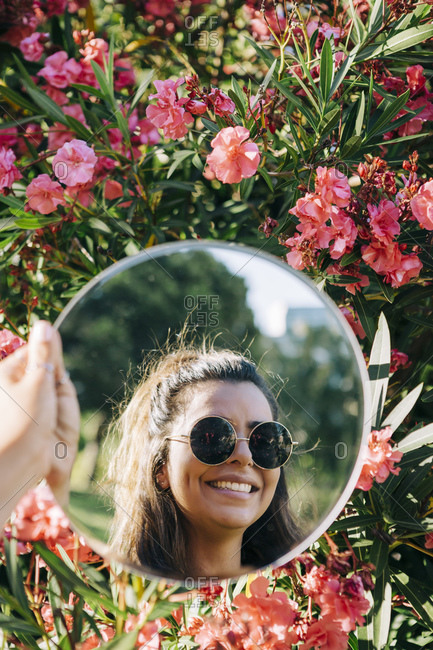 Close-up of young woman wearing sunglasses reflecting of mirror against flowers in park