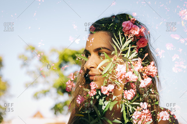 Double exposure of thoughtful young woman and flowers against clear sky