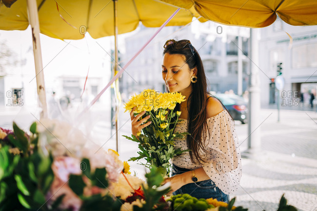 Young woman smelling bouquet of flowers at flower shop