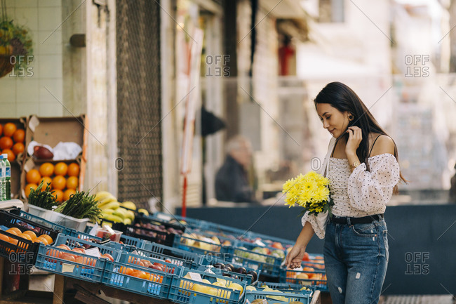 Young woman buying vegetables and fruits at market