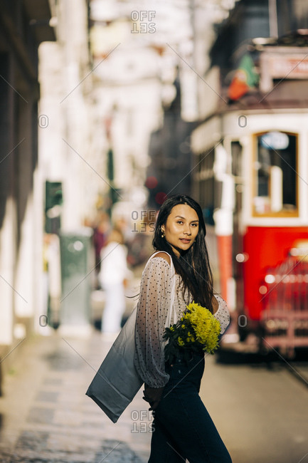 Young woman with bouquet walking in city