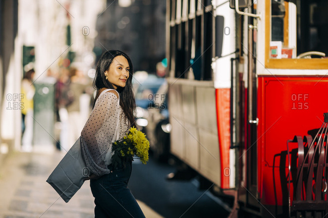 Young woman standing by tram in city