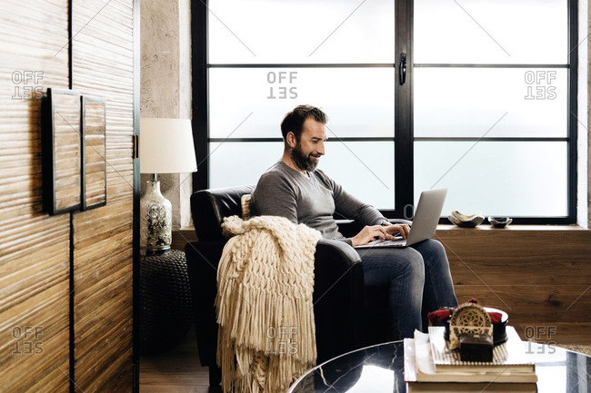 Mature man sitting by window- using laptop- sitting in armchair