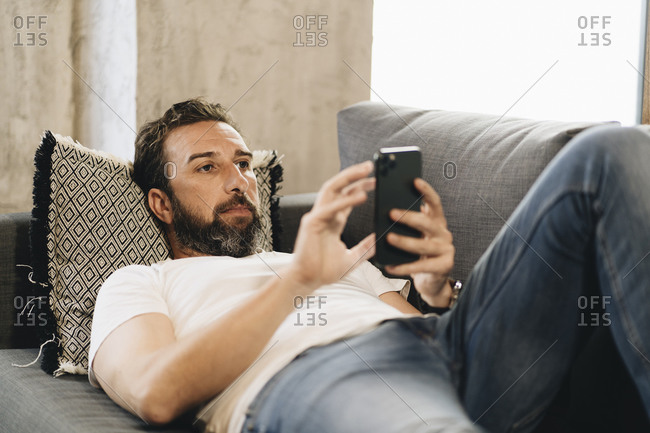Mature man lying on couch- using smartphone