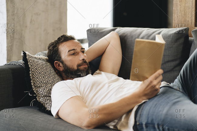 Mature man lying on couch- reading book