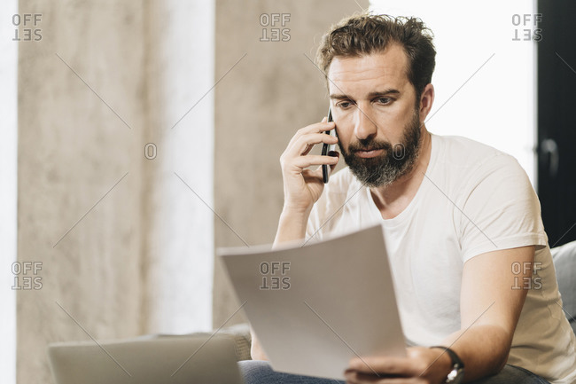 Mature man sitting on couch- talking on the phone- holding papers