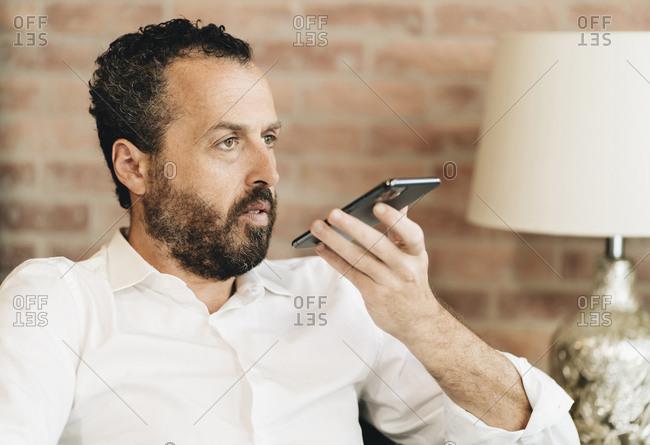 Mature man speaking voice mail in smartphone