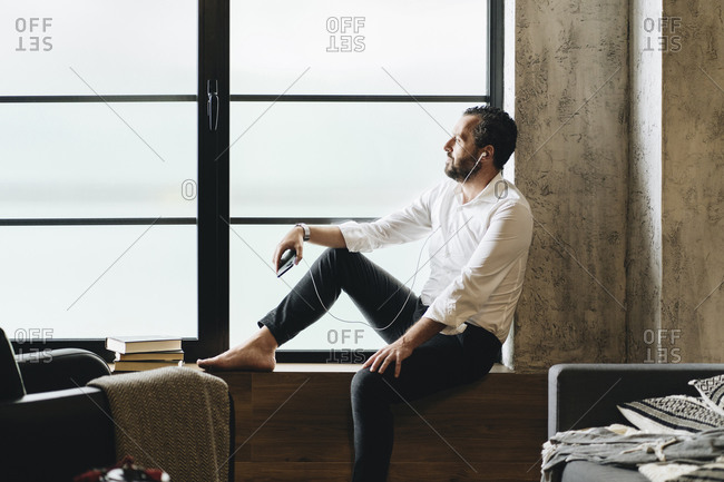 Mature man sitting barefoot on window sill- using smartphone and earphones