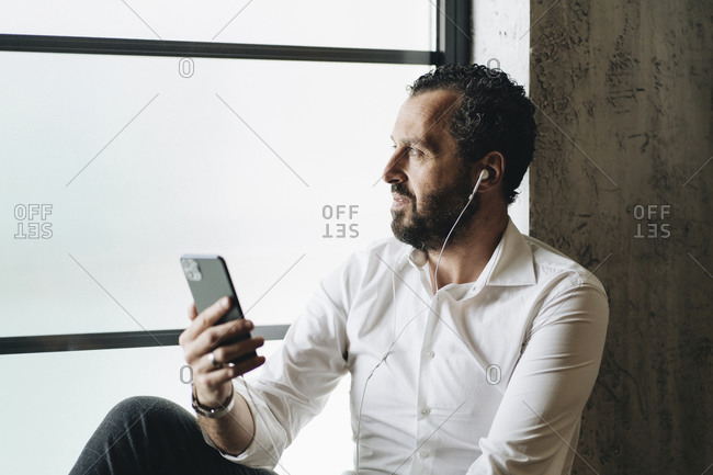 Mature man sitting on window sill- using smartphone and earphones