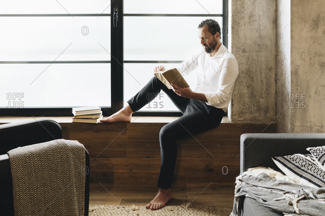 Mature man sitting barefoot on window sill- reading book