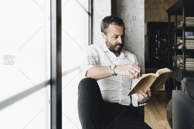 Mature man sitting on window sill- reading book