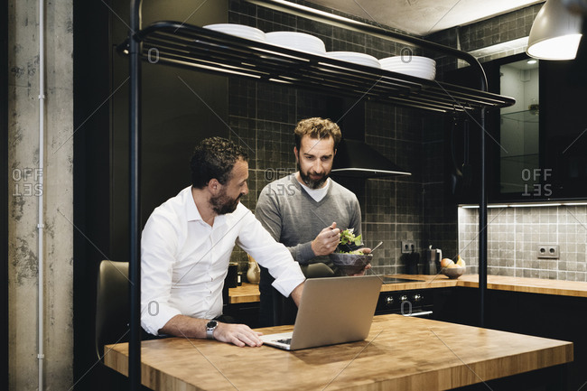 Mature friends working on laptop in kitchen- one eating salad