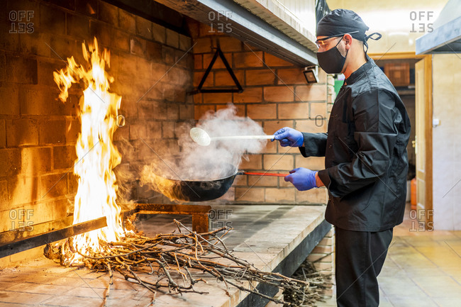 Traditional cooking of paella in restaurant kitchen- chef wearing protective mask