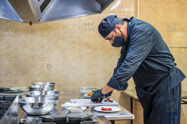 Chef preparing salad on plate