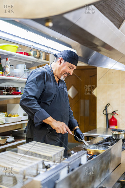 Chef with pan in traditional Spanish restaurant kitchen