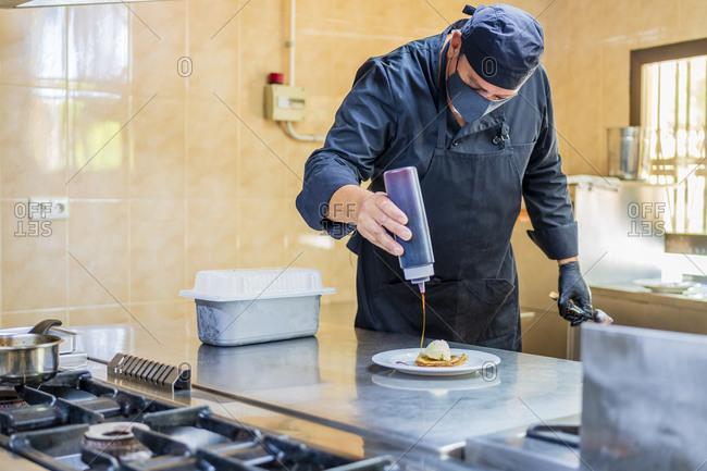 Chef preparing plate with crepe and vanilla ice cream
