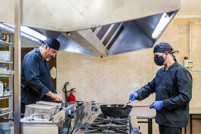 Traditional cooking in restaurant kitchen- chef wearing protective mask