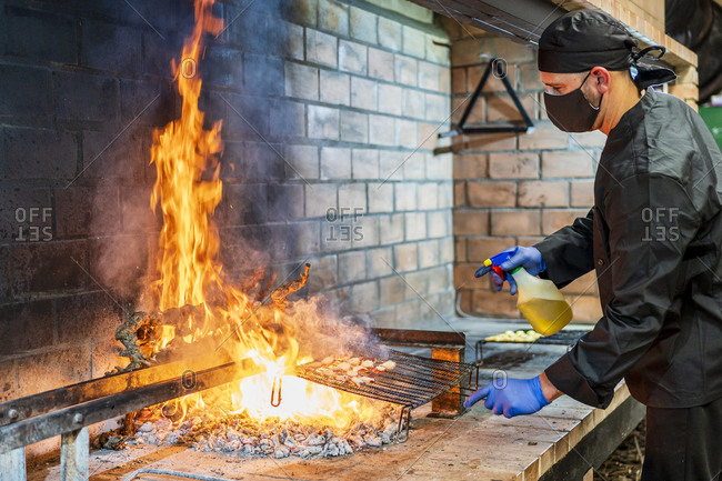 Traditional cooking of seafood on grill in restaurant kitchen- chef wearing protective mask