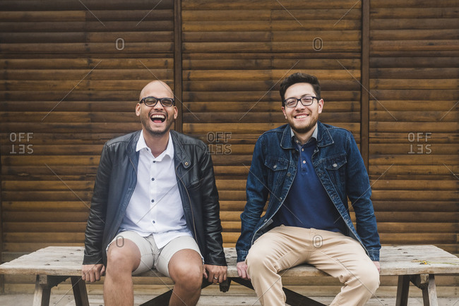 Cheerful gay couple sitting on table against wooden wall