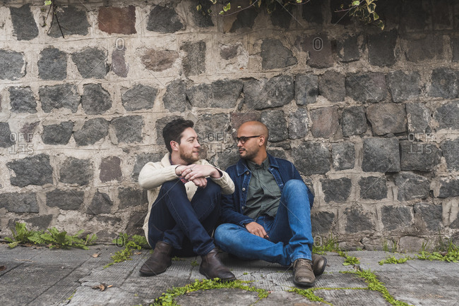Gay couple talking while sitting on footpath against stone wall