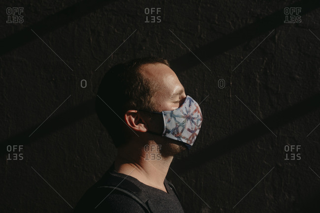 Close-up of mid adult man with eyes closed wearing mask against wall