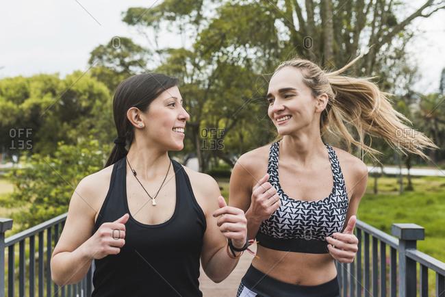 Smiling female friends jogging in park