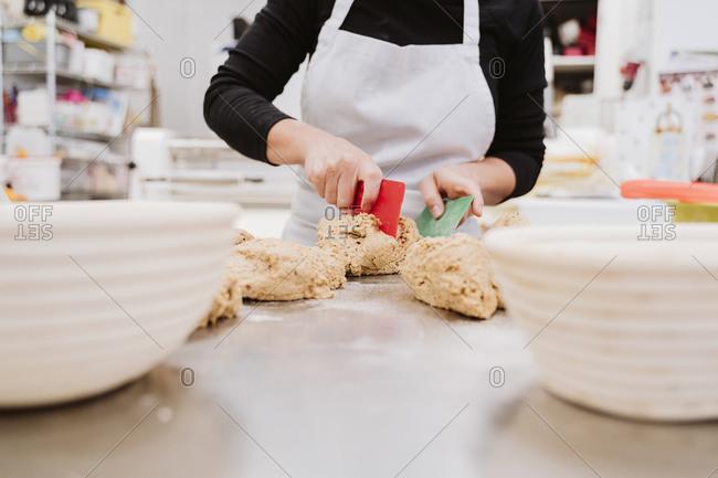 Female baker preparing bread loaf in bakery