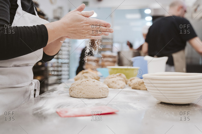 Female baker sprinkling flour on bread dough on kitchen counter in bakery