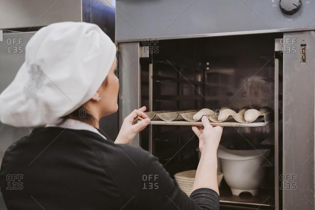 Female baker inserting baking pan in oven at bakery