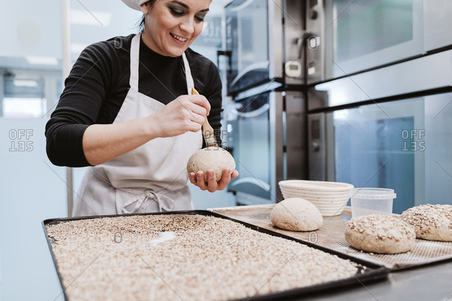 Female baker preparing wholegrain buns at bakery