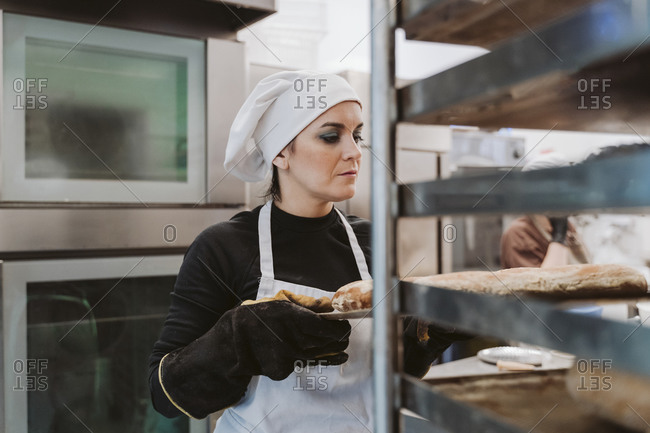 Female baker holding baking tray at bakery