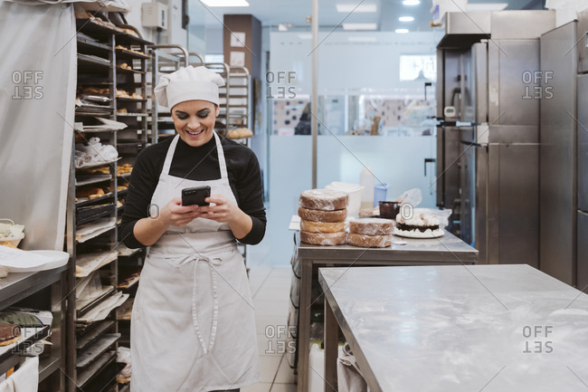 Happy female baker using smart phone in commercial kitchen at bakery