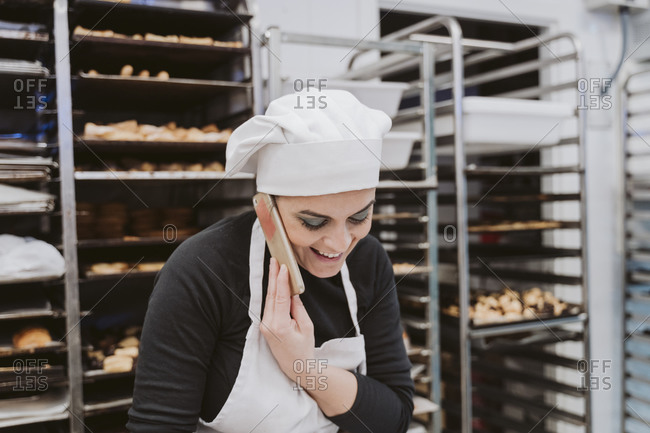 Happy female baker using smart phone in kitchen at bakery