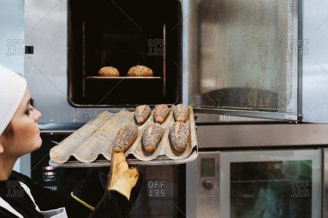 Female baker inserting wholegrain bread on baking pan in oven at bakery