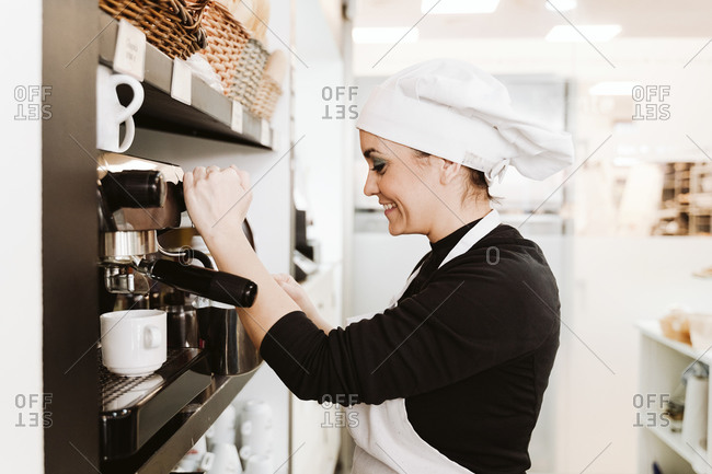Happy baker preparing coffee at bakery