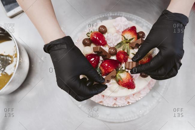Female baker decorating cake on table in bakery