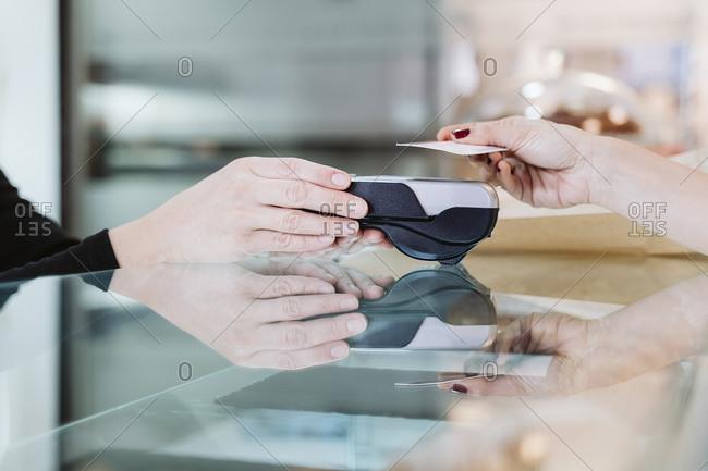 Customer paying through credit card at bakery