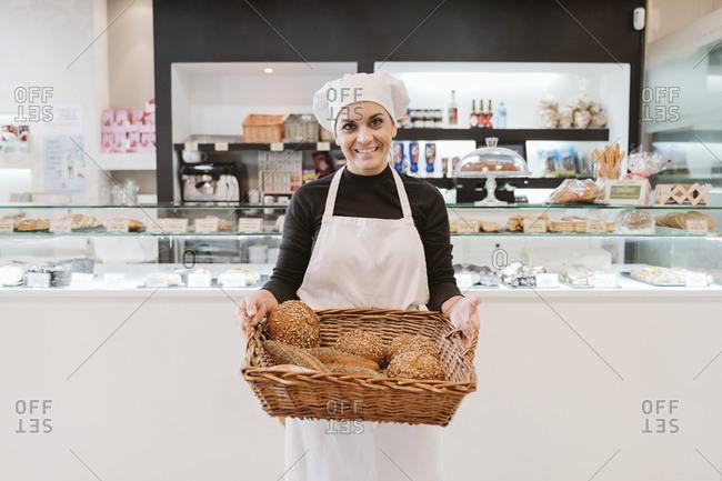 Confident female baker holding breads in wicker basket at bakery