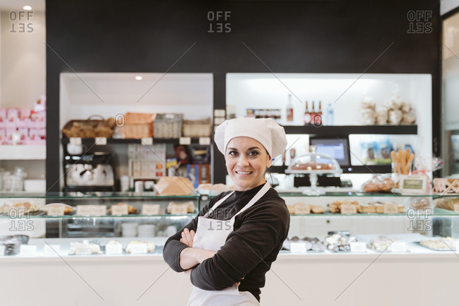 Confident female baker standing arms crossed at bakery