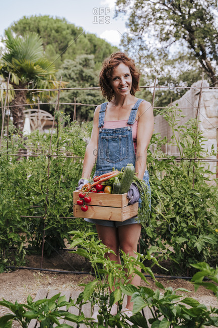Smiling woman holding various vegetables in crate while standing against plants at community garden